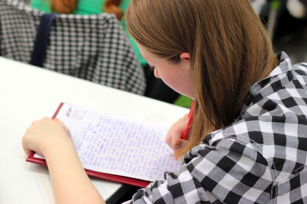 A high school students writes during Writer's Workshop.