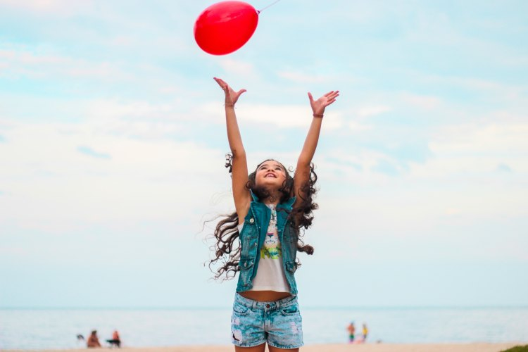 A photo of a girl with a red balloon illustrates a photo for The Sometimes Poem, a poem for high school students.