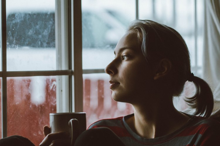 Woman daydreaming while looking out a window.