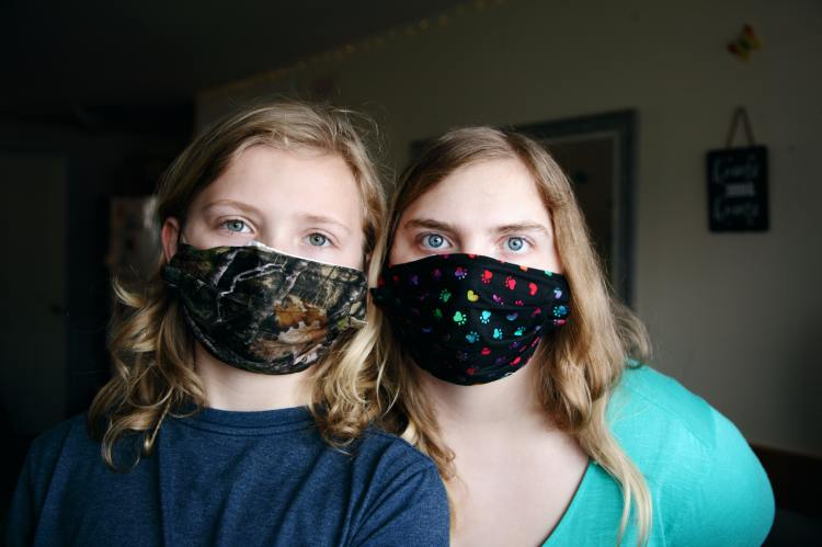 Two girls wearing face masks illustrate a post about corona virus acrostic poems, a type of poem for high school students.