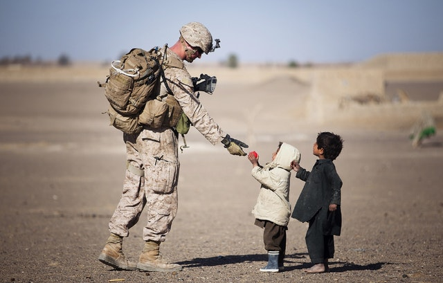 A soldier helps children. Veterans Day poems recognize veterans like this one.