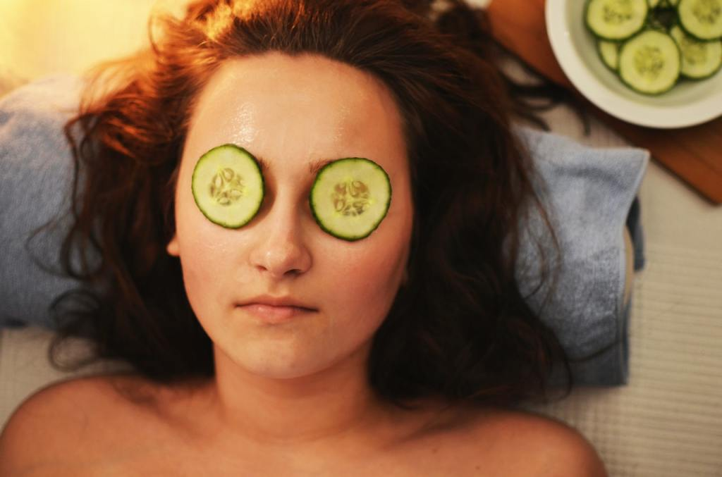 A woman with cucumber slices on her eyes practices teacher self-care.