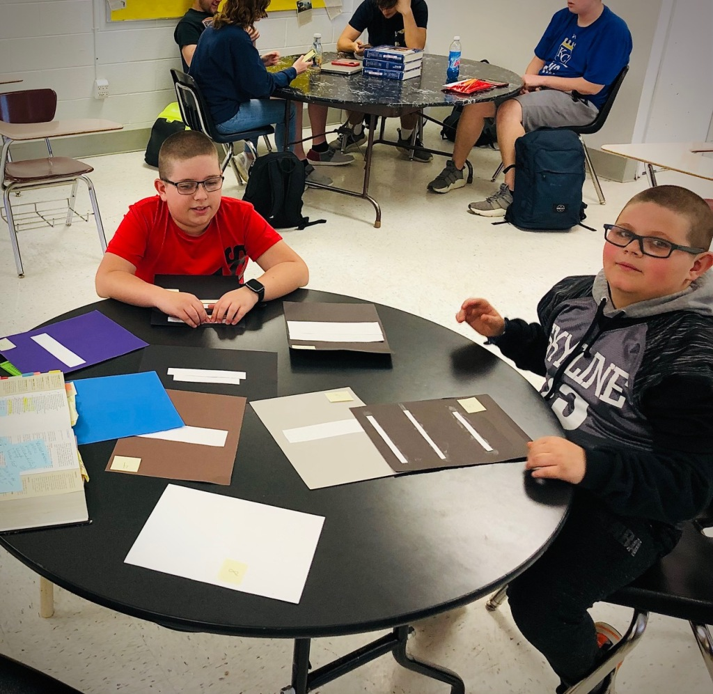 Elementary students read Braille created by high school seniors.