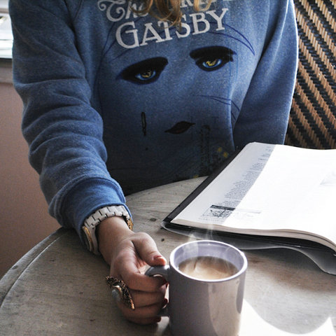 Student drinking coffee while wearing a Great Gatsby sweatshirt.