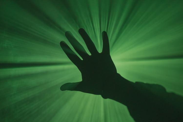 A hand reaching toward a green light