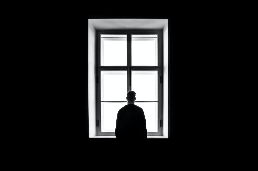 A lone figure is silhouetted standing before a large window